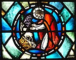 Stained glass image of the Good Shepherd finding lost sheep
